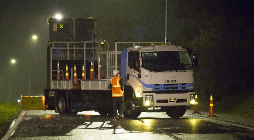 A photo of a truck being instructed by a temporary traffic expert. The rain is pouring and its night time