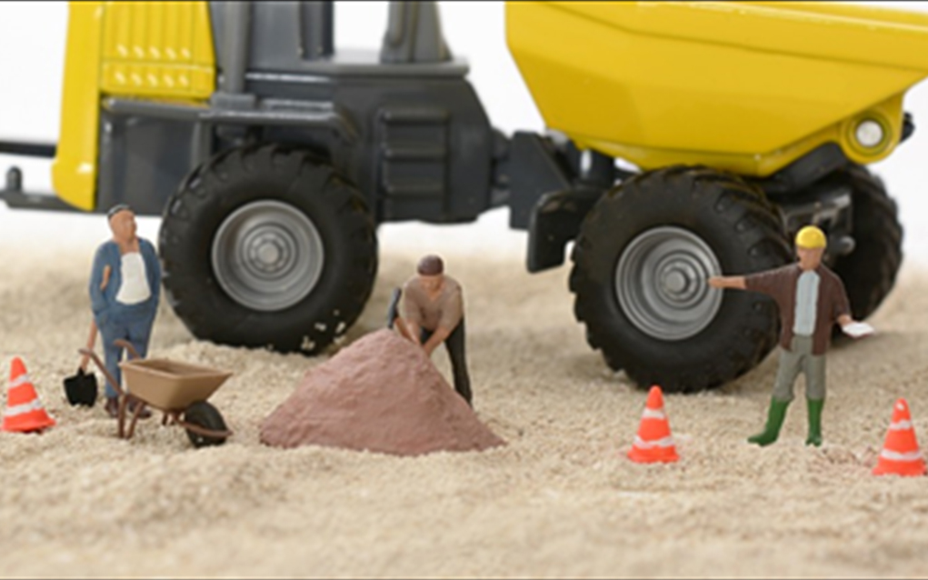 Mini figures of three men doing construction work with Traffic cones and a truck behind them